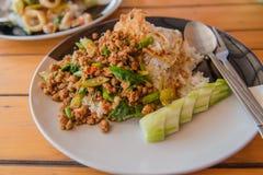 Ris som överträffas med stekt under omrörning griskött och basilika på plattan på trätabellen Royaltyfri Fotografi