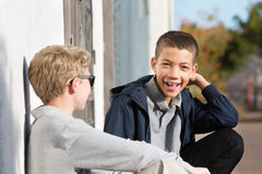 Risa adolescente con los apoyos afuera con el amigo Fotos de archivo libres de regalías