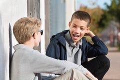Risa adolescente con los apoyos al lado del amigo Imágenes de archivo libres de regalías