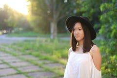 Risa alegre de las emociones de la puesta del sol asiática femenina maravillosa del sombrero Fotos de archivo
