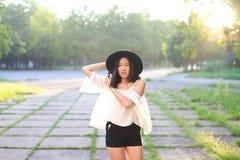 Risa alegre de las emociones de la puesta del sol asiática femenina maravillosa del sombrero Foto de archivo