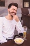 Risa atractiva del hombre joven asentada en una terraza Imagenes de archivo