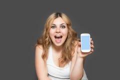 Risa con el adolescente abierto de la boca que muestra un teléfono elegante Imagenes de archivo
