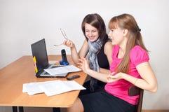 Risa de dos muchachas en trabajo Fotos de archivo libres de regalías