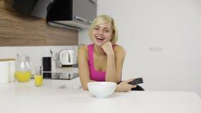 Risa de la sonrisa de la mujer que mira el control de la TV teledirigido almacen de metraje de vídeo