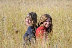Risa de las muchachas en un campo del otoño Foto de archivo libre de regalías