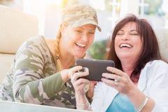 Risa femenina de dos amigos mientras que usa un teléfono elegante Imágenes de archivo libres de regalías