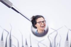 Risa femenina joven alegre en el espejo de un dentista Fotos de archivo