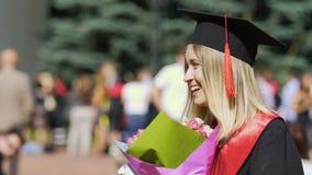 Risa graduada con el ramo de flores en manos, celebración de la hembra feliz almacen de video