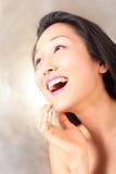Risa modelo en fondo de oro Foto de archivo libre de regalías