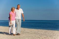 Risa que camina de los pares mayores felices en una playa foto de archivo libre de regalías