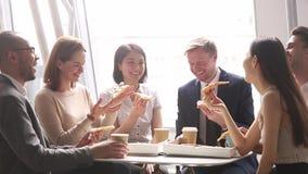 Risa que habla del equipo multicultural feliz del negocio comiendo la pizza en oficina metrajes