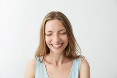 Risa sonriente de la muchacha alegre feliz sincera hermosa con los ojos cerrados sobre el fondo blanco Imagen de archivo