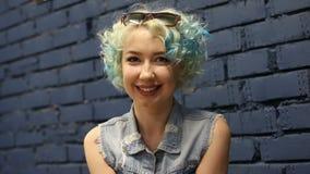Risa sonriente de la muchacha cabelluda rizada feliz alegre joven mirando la cámara sobre fondo de la pared de ladrillo almacen de video