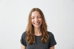 Risa sonriente de la muchacha feliz alegre joven con los ojos cerrados sobre el fondo blanco Imagen de archivo