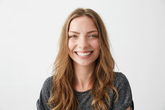Risa sonriente de la muchacha feliz alegre joven mirando la cámara sobre el fondo blanco Fotos de archivo libres de regalías