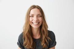 Risa sonriente de la muchacha feliz alegre joven mirando la cámara sobre el fondo blanco Fotografía de archivo libre de regalías