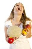 Risas de la muchacha mientras que da fruto el sostenerse Foto de archivo libre de regalías
