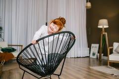 Risas divertidas de la niña del pelirrojo en silla en casa imagen de archivo libre de regalías