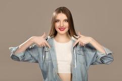 Risas femeninas del adolescente, señalando al espacio vacío Sopycpase Maquillaje brillante y moda hermosos imagen de archivo