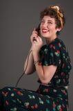 Risas modelas de la muchacha mientras que en el teléfono pasado de moda Foto de archivo