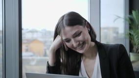 Risas y sonrisas de la mujer joven, sentándose en cafetería en la tabla de madera En la tabla es el ordenador port?til de alumini metrajes