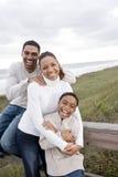 Risata della famiglia del African-American, abbracciante alla spiaggia fotografie stock libere da diritti