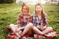 Risata di risata di due una giovane donne dei pantaloni a vita bassa Immagini Stock Libere da Diritti