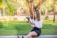 Risata e sorriso felici della donna di affari che leggono un libro fotografie stock