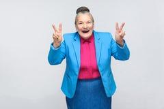 Risata invecchiata della donna e mostrare il segno di vittoria o di pace alla macchina fotografica fotografia stock libera da diritti