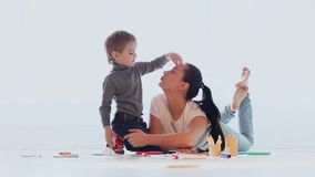 Risate di tiraggio del gioco del figlio e della madre in una stanza bianca stock footage