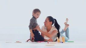 Risate di tiraggio del gioco del figlio e della madre in una stanza bianca video d archivio