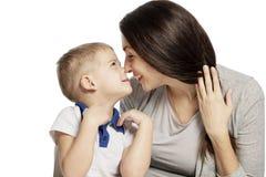 Risate ed abbracci svegli del ragazzino con la mamma, isolata su fondo bianco Tenerezza ed amore fotografia stock libera da diritti