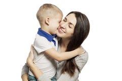 Risate ed abbracci svegli del ragazzino con la mamma, isolata su fondo bianco Tenerezza ed amore immagine stock libera da diritti