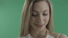 Risatine attraenti adorabili della donna contro fondo verde video d archivio