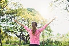 Riscaldamento asiatico della giovane donna il corpo che allunga prima dell'esercizio e dell'yoga di mattina nel parco al di sotto Immagini Stock