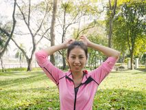 Riscaldamento asiatico della giovane donna il corpo che allunga prima dell'esercizio e dell'yoga di mattina nel parco al di sotto Immagini Stock Libere da Diritti