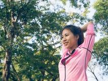 Riscaldamento asiatico della giovane donna il corpo che allunga prima dell'esercizio e dell'yoga di mattina nel parco al di sotto Fotografie Stock