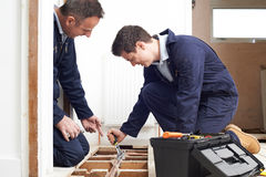 Riscaldamento centrale di And Apprentice Fitting dell'idraulico nella Camera Fotografia Stock