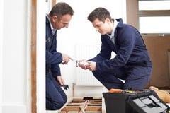 Riscaldamento centrale di And Apprentice Fitting dell'idraulico nella Camera Fotografie Stock