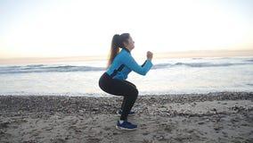 Riscaldamento del corridore della giovane donna prima della presa pareggiare sulla spiaggia archivi video