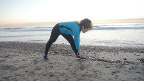 Riscaldamento del corridore della giovane donna prima della presa pareggiare sulla spiaggia stock footage