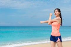 Riscaldamento del corridore della giovane donna sulla spiaggia della spiaggia Immagini Stock Libere da Diritti