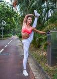 Riscaldamento dell'atleta femminile prima di risolvere allungando le sue gambe che fanno esercizio spaccato stante all'aperto nel Fotografia Stock Libera da Diritti
