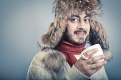 Riscaldamento dell'uomo con la tazza della bevanda calda Fotografia Stock