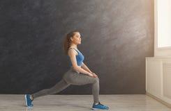 Riscaldamento della donna di forma fisica che allunga formazione all'interno Immagini Stock