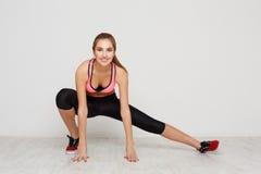 Riscaldamento della donna di forma fisica che allunga formazione all'interno Fotografie Stock