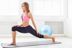 Riscaldamento della donna di forma fisica che allunga formazione all'interno Immagini Stock Libere da Diritti