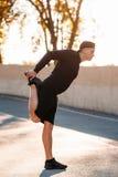 Riscaldamento dello sprinter le sue gambe prima della formazione Fotografie Stock