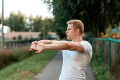 Riscaldamento maschio dell'atleta in natura, via nella città, scaldantesi i muscoli delle mani di estate nel parco vita Fotografia Stock